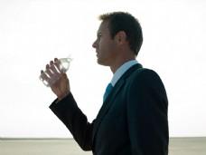 在沙漠中拿着水瓶的商务男士图片