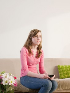 坐在沙发上玩手机的外国女人图片