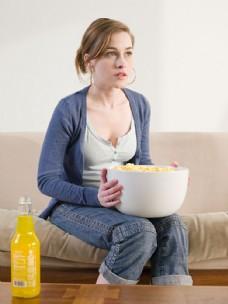 坐在沙发上捧着容器的外国女人图片