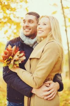 拿着枫叶叶子的情侣图片