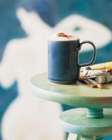 桌子上摆放的颜料和咖啡图片