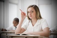 手拿铅笔思考的女学生图片